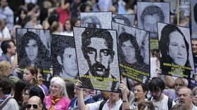 Demonstranten halten Fotos von Opfern in die Luft: Um ihren Widerstand gegen Diktaturen zu verdeutlichen, sind in Buones Aires Zehntausende auf die Straße gegangen. Quelle: AP