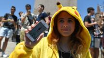 A gamer dressed up like a Pokemon shows her mobile phone as people use the Pokemon Go application on their mobiles in central Rome on July 19, 2016. Since its launch two weeks ago, the game for mobile gadgets has sparked a worldwide frenzy among users who have taken to the streets with their smartphones. The free app uses satellite locations, graphics and camera capabilities to overlay cartoon monsters on real-world settings, challenging players to capture and train the creatures for battles. / AFP PHOTO / TIZIANA FABI Quelle: AFP