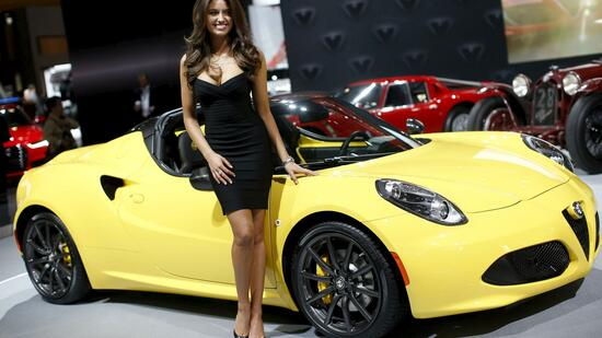 A model poses next to an Alfa Romeo sports car at the 2015 New York International Auto Show in New York City
