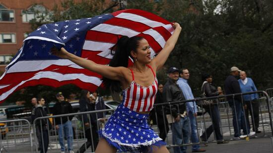 huGO-BildID: 23822486 A woman holds up a U.S. flag while she skates near protestors and members of Occupy Wall Street before the march in the annual demonstration calling for a stop to police brutality in New York October 22, 2011. REUTERS/Eduardo Munoz (UNITED STATES - Tags: BUSINESS CIVIL UNREST) Quelle: Reuters