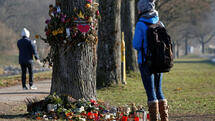 A woman looks at flowers and messages attached on a tree near the site where a 19-year-old female student died on October 15, in Freiburg, Germany December 6, 2016. REUTERS/Vincent Kessler Quelle: Reuters