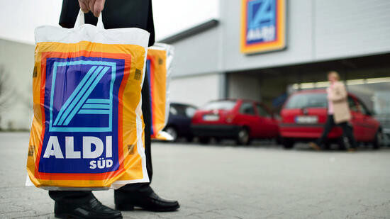 huGO-BildID: 12971655 A man with a shopping bag stands infront of a Aldi supermarket in Ettlingen, Germany, 22 March 2005. German supermarket discounters Aldi and Lidl are expanding and entering the market in Switzerland with their low-budget products. Foto: Martin Rütschi +++(c) dpa - Report+++ Quelle: picture-alliance/dpa