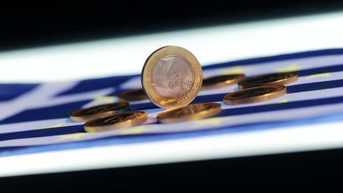 Auf einer Griechenlandfahne liegen Euro-Münzen. Quelle: dpa