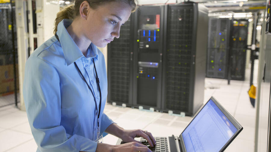 Server room technician studying laptop screen Quelle: Getty Images