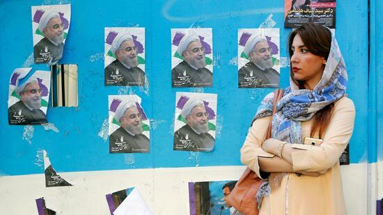 Eine Iranerin in Teheran vor Wahlplakaten des Reform-Präsidenten Hassan Ruhani. Quelle AFP