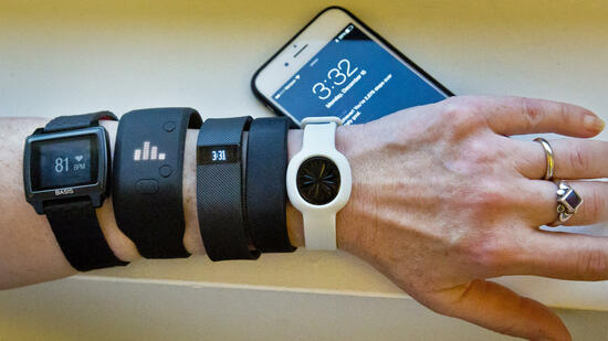 FILE - In this Dec. 15, 2014, file photo, fitness trackers, from left, Basis Peak, Adidas Fit Smart, Fitbit Charge, Sony SmartBand, and Jawbone Move, are posed for a photo next to an iPhone, in New York. Although sales of fitness trackers are strong, many of their owners lose enthusiasm for them once the novelty wears off. (AP Photo/Bebeto Matthews, File) Quelle: AP
