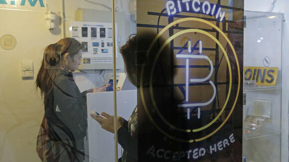 FILE - In this Friday, Dec. 8, 2017, file photo, people use a Bitcoin ATM in Hong Kong. The public's intense interest in all things bitcoin, and efforts by entrepreneurs to fund their businesses with digital currencies, has begun to draw attention from regulators. (AP Photo/Kin Cheung, File) Quelle: AP