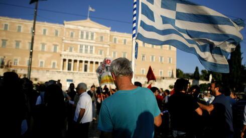 Ein Mann trägt eine griechische Flagge bei Protesten in Athen. Griechenland könnte in diesem Jahr weitere Milliarden-Hilfen brauchen. Quelle: dpa