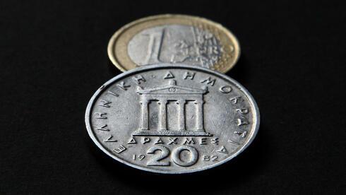Eine griechische 20 Drachmen-Münze und eine Euro-Münze. Quelle: dpa