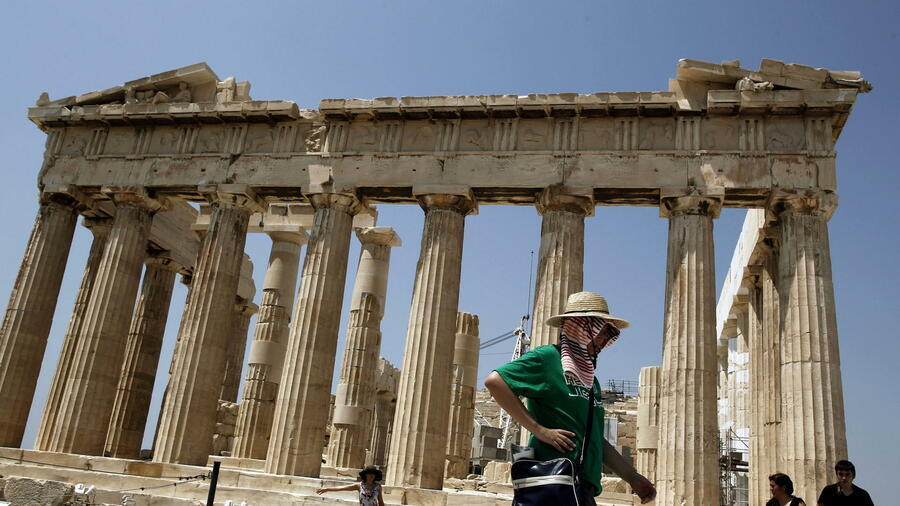 huGO-BildID: 27121815 epa03303632 A tourist tries to protect herself from the sun as she walks past the Parthenon Temple in Athens, Greece, 11 July 2012. Temperatures in the Greek capital reached 40 degrees Celsius, reports state. EPA/ALKIS KONSTANTINIDIS +++(c) dpa - Bildfunk+++ Quelle: dpa