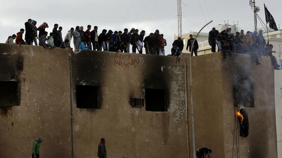 huGO-BildID: 21030077 Libyan protesters stand atop a damaged police station as they burn an effigy of Libyan leader Moammar Gadhafi during a demonstration, in Tobruk, Libya, Wednesday Feb. 23, 2011. Thousands in the coastal town of Tobruk celebrated their freedom from Moammar Gadhafi on Wednesday by waving flags of the old monarchy, honking horns and firing guns in the air around a city square where he once executed people. (Foto:Hussein Malla/AP/dapd) Quelle: dapd
