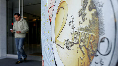 Plakat mit Euro-Münzen-Aufdruck. Quelle: ap