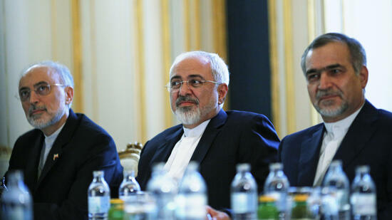Iranian Foreign Minister Mohammad Javad Zarif and the Head of the Iranian Atomic Energy Organization Ali Akbar Salehi (L) meet with U.S. Secretary of State John Kerry (not pictured) at a hotel in Vienna, Austria
