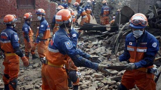 Japanese rescue team members work to clear debris while searching for victims after last week's earthquake in Lalitpur