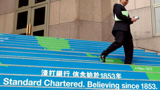 huGO-BildID: 2236481 A man walks down the steps of Standard Chartered Bank building in Hong Kong Monday, Oct. 21, 2002, as emerging markets bank Standard Chartered PLC began promotion of a share listing in Hong Kong that is expected to raise up to 3.19 billion Hong Kong dollars (US$409 million). London-listed Standard Chartered has focused on raising its profile throughout the developing world, especially in Asia, and the secondary listing in Hong Kong is a part of that strategy.(AP Photo/Vincent Yu) Quelle: ap