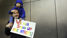 Matt Sernett holds his daughter Wade, 5, atop his shoulders, as more than 1,000 people gather at Seattle-Tacoma International Airport, to protest President Donald Trump's order that restricts immigration to the U.S., Saturday, Jan. 28, 2017, in Seattle. (Genna Martin/seattlepi.com via AP) Quelle: AP