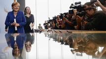 Photographers and television cameras cover German Chancellor Angela Merkel as she leaves a news conference in Berlin, Germany, Thursday, July 28, 2016. Second left is Angela Wefers, the journalist who led the news conference. (AP Photo/Markus Schreiber) Quelle: AP