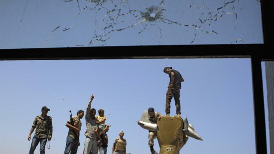Nach der Einnahme von Bab el Asisija bestiegen die Rebellen Gadaffis Blechskulptur - eine goldene Faust, die ein amerikanisches Flugzeug zerquetscht. Quelle: dapd