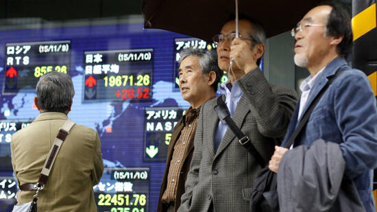 Passers-by stand in front of Japan's Nikkei stock index and other financial indexes displayed on an electronic board in Tokyo Tuesday, Nov. 10, 2015.