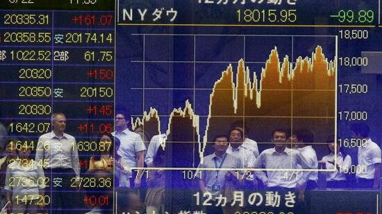 People are reflected in an electronic board displaying market indices in Tokyo