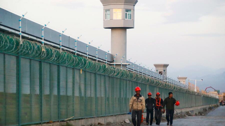"""Arbeiter vor einem offiziell als """"Umerziehungslager"""" eingestuftem Lager. in Dabancheng in der Xinjiang Provinz in China. Die USA behaupten, die Chinesen würden bis zu drei Million muslimische Uiguren in solchen Lagern internieren, um sie """"vom Extremismus abzubringen"""". Quelle: Reuters"""