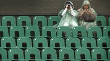 Spectators dressed in waterproof clothing wait for the rain to stop at the Wimbledon tennis Championships June 29, 2001. Play at the All England Lawn Tennis Club was interupted for the second day running by bad weather. REUTERS/Dan Chung Quelle: Reuters