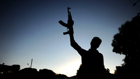 Ein syrischer Rebell hält in Aleppo eine Waffe hoch: Die EU-Außenminister beraten über Waffenlieferungen an die Aufständischen in Syrien. Quelle: dpa