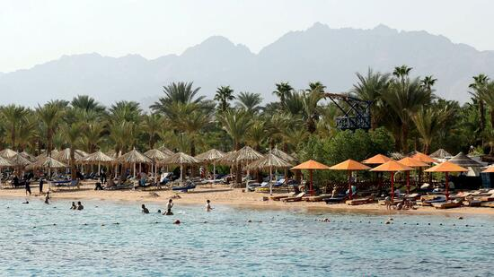 Tourists swim in the sea in the Red Sea resort of Sharm el-Sheikh