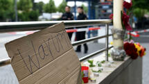 "A poster reads ""Why? (Warum?)"" near flowers and candles to commemorate victims at the entrance of the subway station near the shopping mall Olympia Einkaufzentrum OEZ in Munich on July 23, 2016, a day after a gunman went on a shooting rampage, killing eight people in a suspected terror attack. The southern city was in lockdown after the shootings, which saw panicked shoppers fleeing the Olympia mall as armed anti-terror police roamed the streets in search of assailant. / AFP PHOTO / Christof Stache Quelle: AFP"