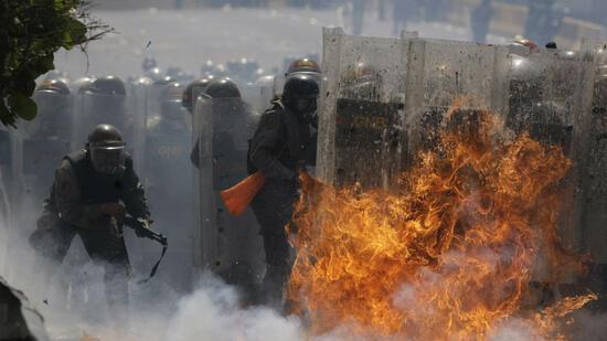 Demonstranten bewerfen venezolanische Polizisten mit Kot