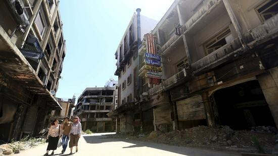 Women walk past damaged buildings along a street in the old city of Homs