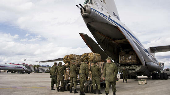 FILE - In this Wednesday, Jan. 20, 2016 file photo, Russian air force personnel prepare to load humanitarian cargo on board a Syrian Il-76 plane at Hemeimeem air base in Syria. Russia's defense ministry said Tuesday, March 15, 2016 that the first group of warplanes stationed at the Russian air base in Syria has left for home following a pullout order from President Vladimir Putin. (AP Photo/Vladimir Isachenkov, File) Quelle: AP